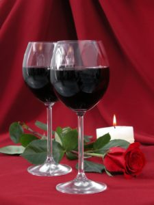 wineglasses, rose and burning candle